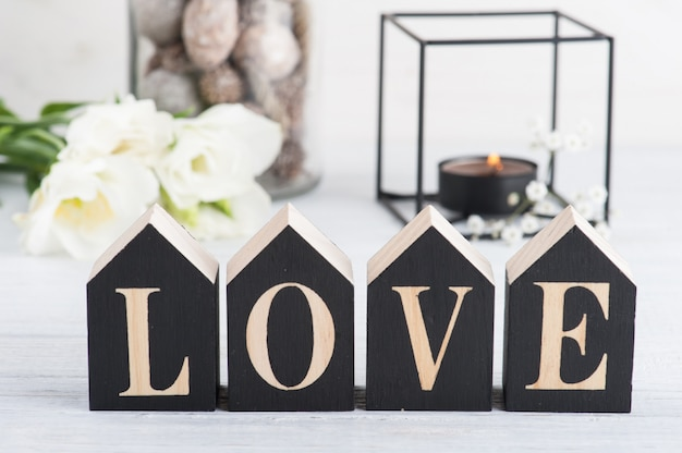 花と点灯ろうそくと木製の手紙愛