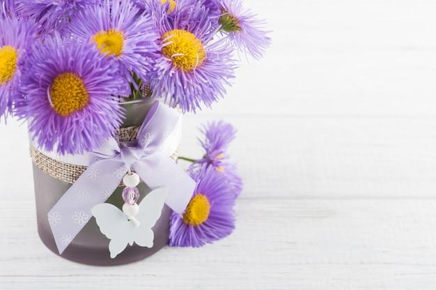 Фиолетовые ромашки на белом столе