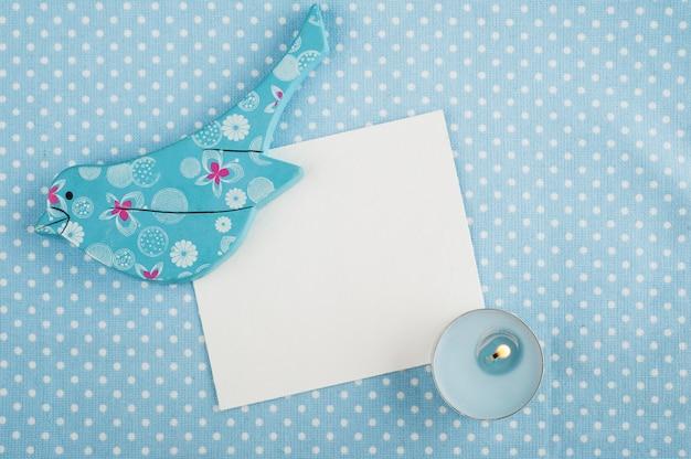 Голубая салфетка, открытка, деревянная птица и свеча, место для текста