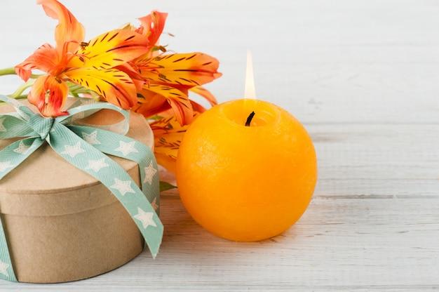 オレンジ色のユリの花とキャンドル、ギフトボックスの配置