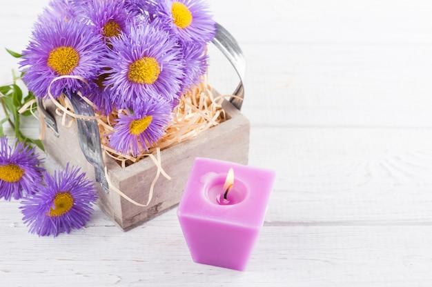 Фиолетовые ромашки и зажженная свеча на белом столе