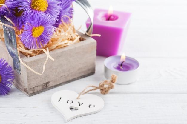 Фиолетовые ромашки и зажженные свечи на белом столе