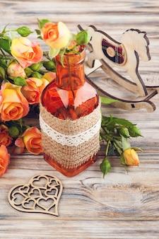 Свежие оранжевые розы цветы, сердце и декор бутылки