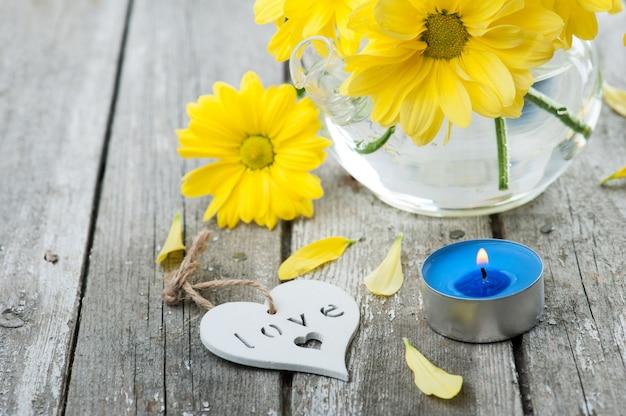 新鮮な黄色のデイジーの花、サイン愛と点灯ろうそく