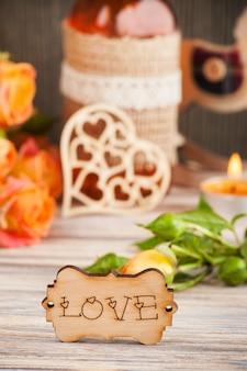 Свежие оранжевые розы, цветы, сердце, декор бутылки и зажженная свеча