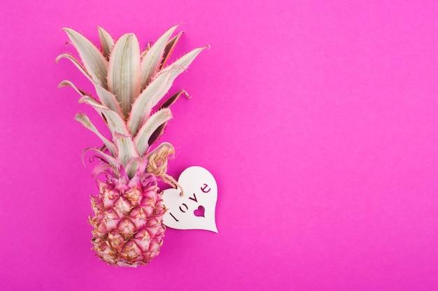 Розовый ананас на розовой поверхности