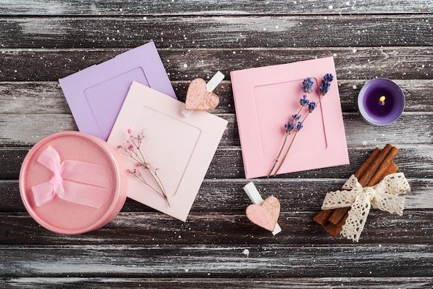 Пустые розовые фиолетовые рамки для фотографий, подарочная коробка и свеча, вид сверху