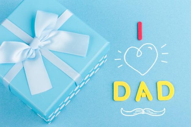 お父さんのことが好きだ。弓で青いギフトボックス。父の日のコンセプト