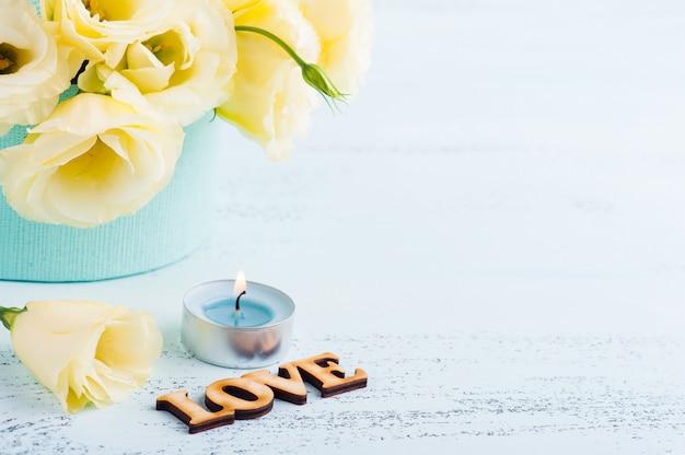 Желтые цветы эустомы, горит синяя свеча фон