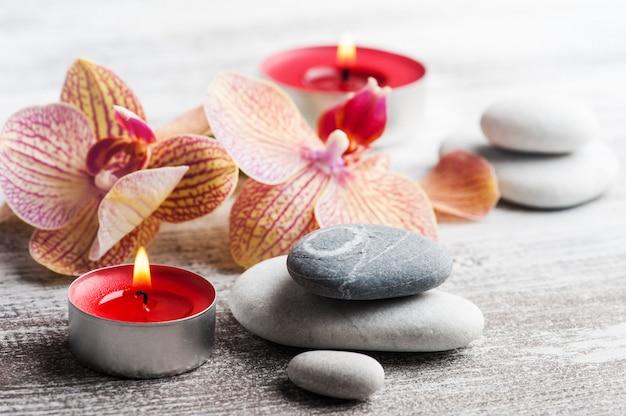 スパ小石と赤オレンジ蘭のある静物
