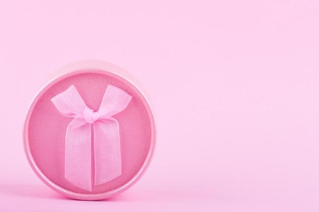 紙の背景にピンクの丸いギフトボックス