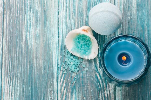 Ванна бомбы крупным планом с голубой зажженной свечой