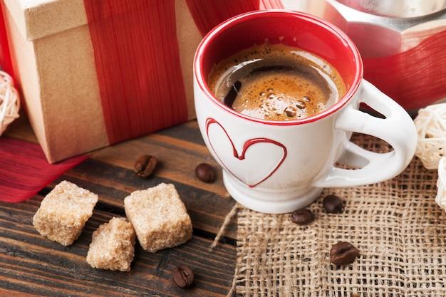 一杯のコーヒーとギフトに赤いリボン