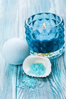 Ванна бомба крупным планом с голубой зажженной свечой