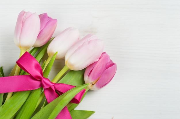 Красные розовые тюльпаны с красной лентой
