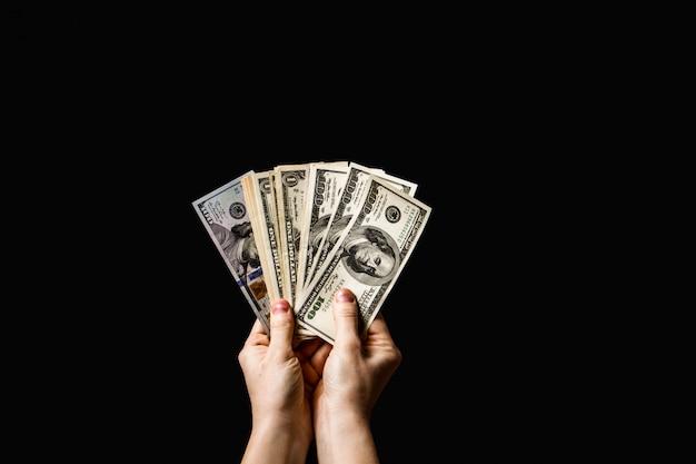 暗い背景上の手の中のお金ドル