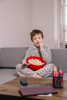 ソファでリラックスしながら大きな赤いボウルでポップコーンを食べる少年
