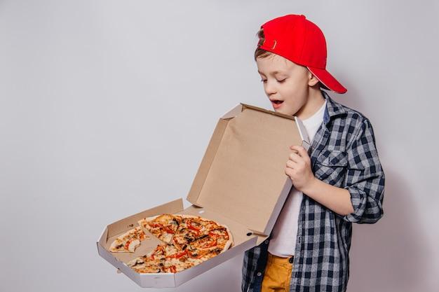 Парень с большим энтузиазмом и нетерпением открывает коробку пиццы на белом фоне