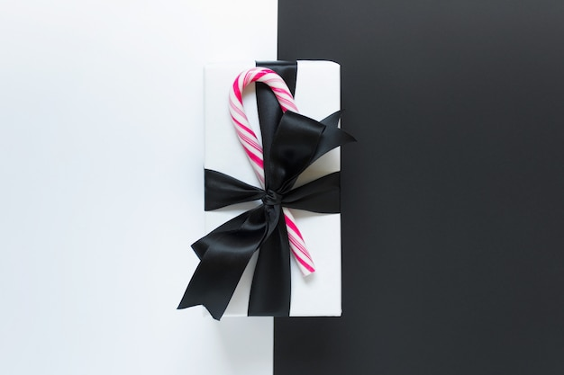 Одиночный подарок с черным атласным бантом и конфетами на двойном фоне