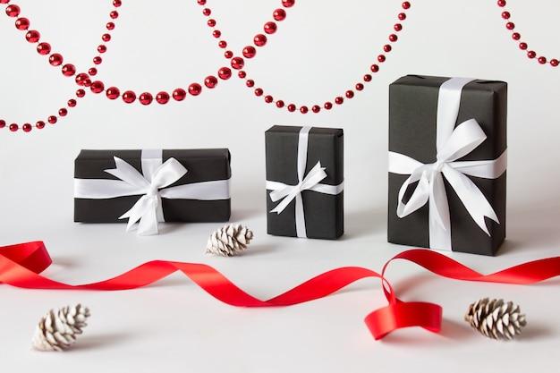 Рождественский зимний фон в красно-белых тонах с подарками и шишками