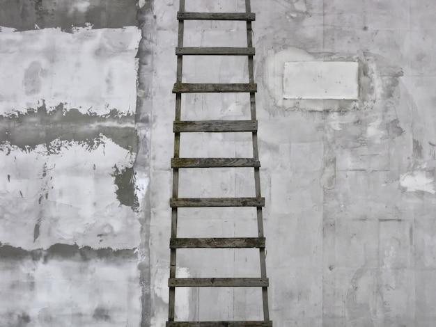 ミニマルなスタイルで灰色の織り目加工プラスター壁の背景に木製のはしご。