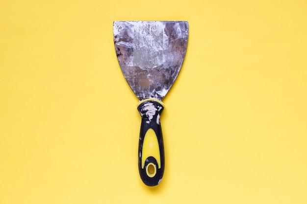 古い石膏の痕跡と汚れた充填パテナイフを使用
