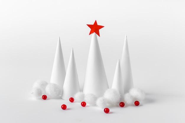 赤いボールと赤い星で飾られた白いクリスマス紙の木
