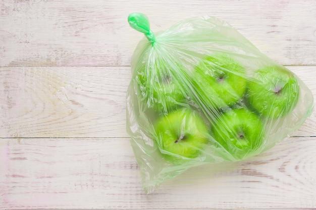木製のテーブルの上のビニール袋に新鮮な青リンゴ。プラスチックの非生態学的使用の環境概念