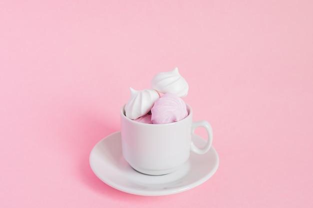 Белый и розовый витой безе в небольшой фарфоровой чашки кофе на розовом фоне. французский десерт, приготовленный из взбитых с сахаром и запеченных яичных белков. открытка с копией пространства