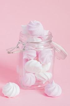 ピンクの背景のガラスの瓶に白とピンクのツイストメレンゲ。砂糖と焼き卵白でホイップしたフランスのデザート。