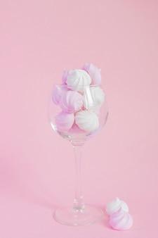 ピンクの背景のつるガラスに白とピンクのツイストメレンゲ。砂糖と焼き卵白でホイップしたフランスのデザート。コピースペースとグリーティングカード