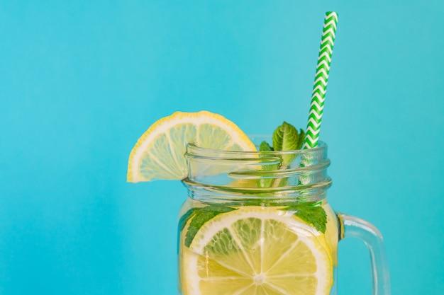 背景色が水色のレモン、ミント、紙ストローで自家製レモネードのメイソンジャーガラス。夏の爽やかな飲み物。