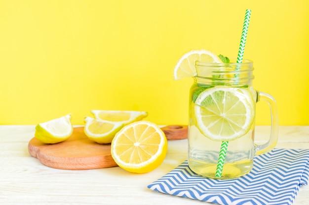 Цитрусовый лимонад вода с нарезанным лимоном и мятой, здоровый и детокс водный напиток летом на деревянный стол с желтым фоном