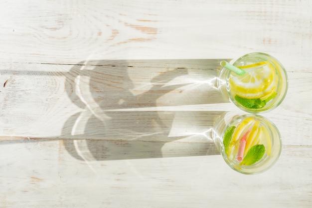 Стекло домодельного лимонада с лимонами, мятой и бумажными соломами на деревянной деревенской предпосылке. летний освежающий напиток. жесткие тени