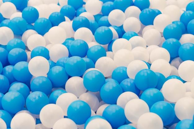 遊び場の乾燥プールでプラスチックの白と青のボールのクローズアップ