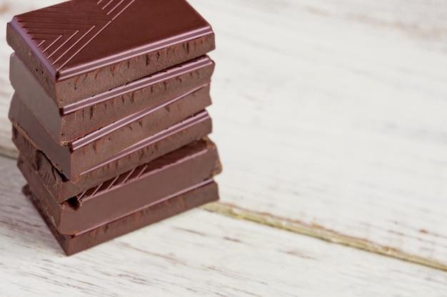 木製のテーブルにチョコレートバー。ダークチョコレートの破片。食品の背景