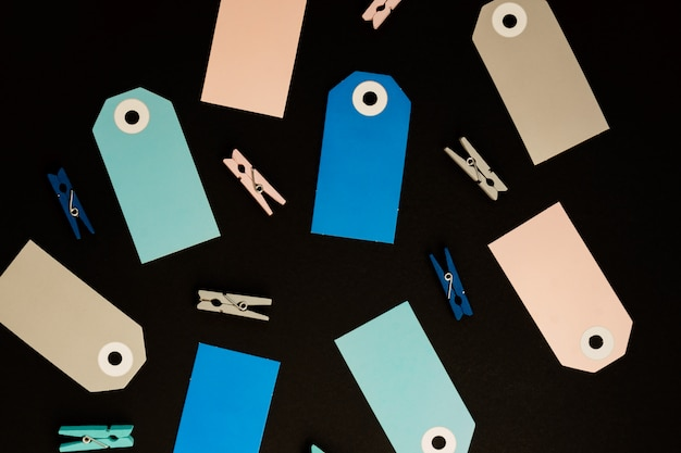 プレゼント用の青、グレー、ピンクの紙カードタグと装飾用の木製洗濯はさみの背景。
