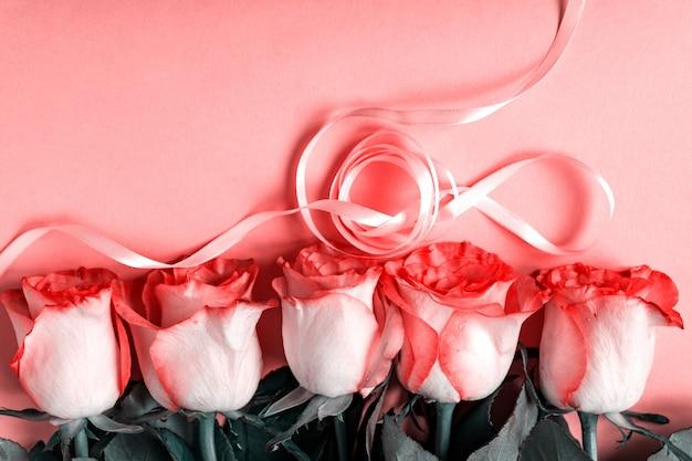 パステルピンクの背景にリボンとピンクの咲くバラ。ロマンチックな花のフレーム。コピースペース
