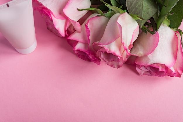 Розовые цветущие розы и крем для лица на пастельных розовом фоне. романтический уход за кожей цветочная рамка. копировать пространство