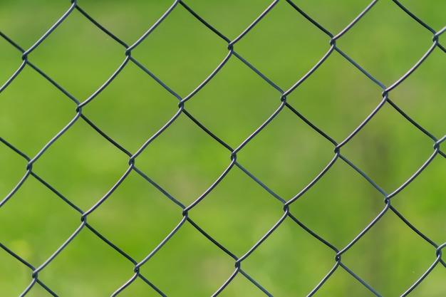 緑の芝生の背景に金属チェーンリンクフェンス