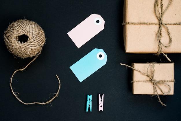 Подарочные коробки ручной работы, завернутые в крафт-бумагу, с синей бумажной карточкой, веревкой и деревянными прищепками для украшения.