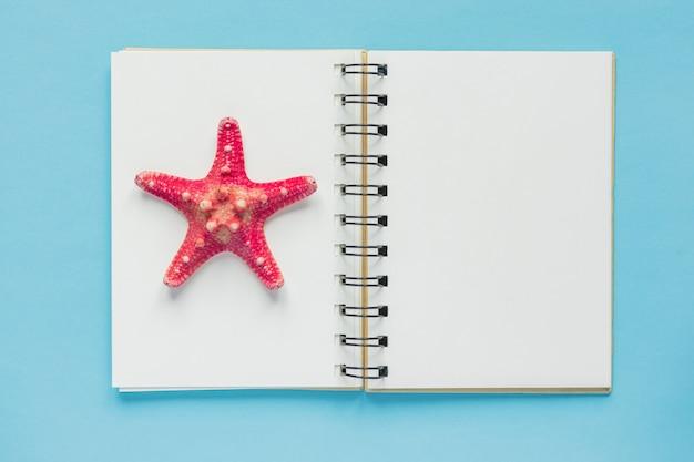 ヒトデと開いている空のノートブックの平面図。旅行および休日の概念
