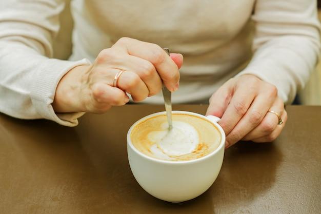 Женская рука перемешивания чашку кофе. утренний свежеприготовленный капучино