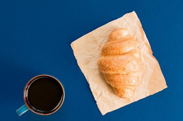 コピースペースでペーパークラフトにブラックコーヒーとクロワッサンのカップの平面図です。フランス風の朝の朝食。