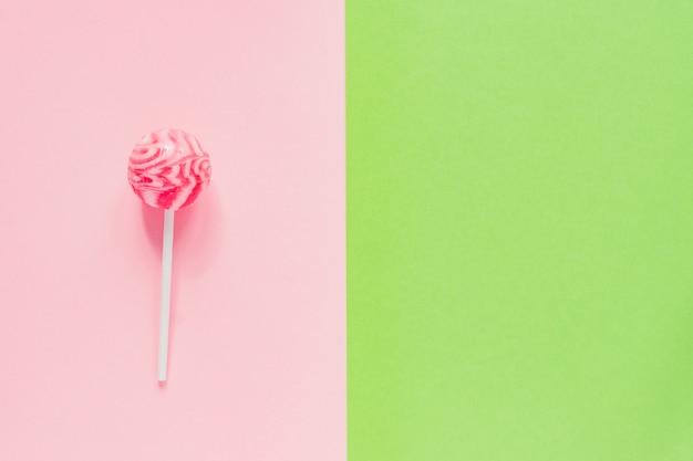 緑とピンクの背景に甘いおいしいピンクロリポップ。コピースペースを備えた最小限のフラットレイアウト