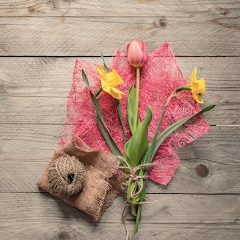 春の花の花束の平面図です。黄色い水仙とピンクのチューリップ。コピースペース。
