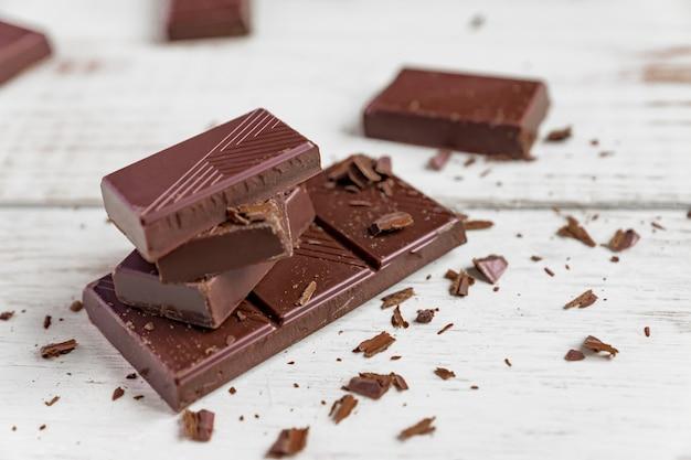 木製のテーブルの上のチョコレートバー。ダークチョコレートの破片