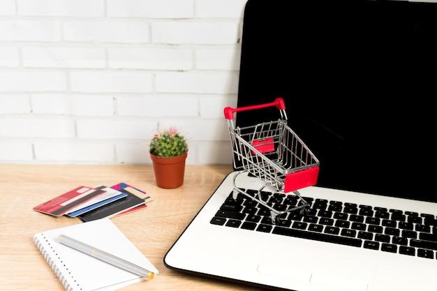 Малая красная магазинная тележкаа или вагонетка на клавиатуре компьтер-книжки. технологический бизнес интернет-магазин концепции