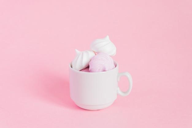 ピンクの小さな磁器のコーヒーカップに白とピンクのねじれたメレンゲ