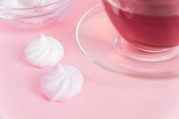 Белые и розовые витые безе и чашка чая на розовом
